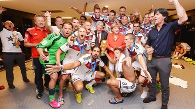 Head Coach Joachim Loew of Germany celebrates with players and German President Angela Merkel in the Germany dressing room (FIFA.com photo)