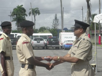 Tactical Services Unit (TSU) rank Griffith (L) receives his award from Police Commissioner Seelall Persaud (R)