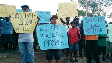 Scores of squatters greeted APNU MP Joseph Harmon with placards held high (Photo by Chevy Devonish)