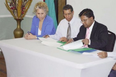 Finance Minister Dr Ashni Singh (right) and Chief Executive Officer of  the Guyana Bank for Trade and Industry, John Tracey (centre)  signing the $60M Rupununi Innovation Fund in the presence of Inter= American Development Bank Country Representative  Sophie Makonnen. (GINA photo)