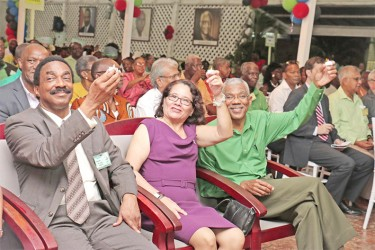 """PNCR leader David Granger (right), his wife, Sandra  (centre) and party Chairman Basil Williams raise makeshift candles during an interpretive dance to the song """"Carry your Candle."""""""