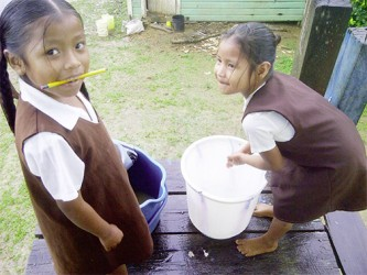 Two schoolchildren washing up for lunch at the hot meal dining house