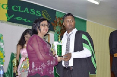 A graduate collects his prize and trophy from Mrs Alli Baksh, wife of the Minister in the Ministry of Agriculture, Alli Baksh. (GINA photo)
