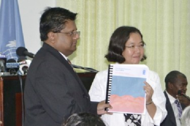 Chisa Mikami, Resident Representative (ag), UNDP (right), officially handing over a copy of the UNDP's Human Development 2014 Report to Finance Minister, Dr. Ashni Singh last week. (GINA photo)