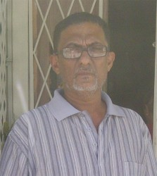 Shaheed Hack standing at the door of his home where he saw his wife robbed