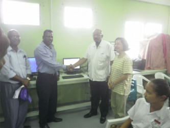 Regional Chairman Parmanand Persaud (second from left) and Minister Norman Whittaker shake hands as the ICT hub is commissioned. Looking on second from right is Acting UNDP Representative, Chisa Mikami.
