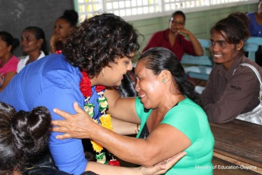 Embrace (pic) Education Minister Priya Manickchand reaching to embrace a parent at the Aurora Primary School. (Ministry of Education photo)