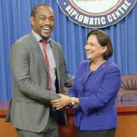 Former Soca Warrior Brent Sancho and Prime Minister Kamla Persad-Bissessar shake hands at the Diplomatic Centre yesterday after she announced that the Government will pay US$1.3million which was owed to members of the team that qualified for the 2006 World Cup
