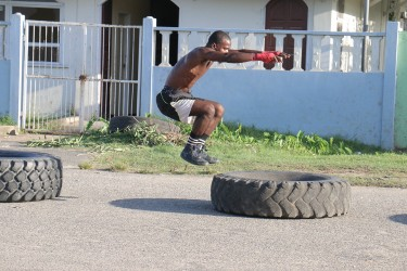 An amateur boxer doing squats on tyres along Independence Boulevard, Albouystown today.