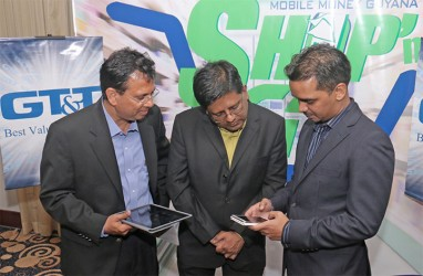 Eshwar Thakurdin, Managing Director of GT&T's Mobile Money Guyana Inc, demonstrates the new Shop'n Go service for GT&T CEO RK Sharma (left) and Finance Minister Dr Ashni Singh. (Photo by Arian Browne)