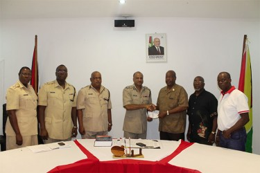 Leon Gibbons (third from right) making the presentation to Police Commissioner Seelall Persaud (Guyana Police Force photo)