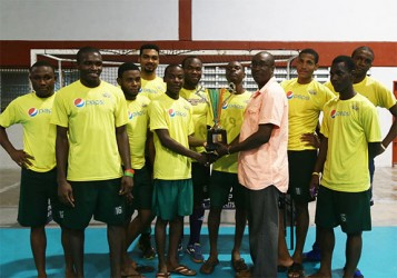Captain Robert France of Pepsi Hikers collecting the division-A championship trophy from Guyana Hockey Board (GHB) Executive Ivor Thompson while other members of the team look on