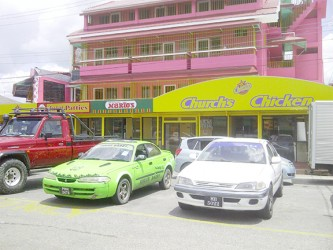 A fleet of hire cars parked in front of the fast food franchises located at Bukhan's rental complex
