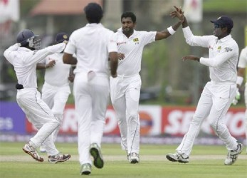 Sri Lanka's Dhammika Prasad (C) celebrates with teammates captain Angelo Mathews (R) and Kaushal Silva (L) after taking the wicket of Pakistan's Ahmed Shehzad (not pictured) during the first day of their first test cricket match in Galle yesterday.CREDIT: REUTERS/DINUKA LIYANAWATTE