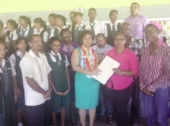 Minister of Education Priya Manickchand (centre) hands over a project outline for the extension of the West Demerara Secondary School to a staff member of the school
