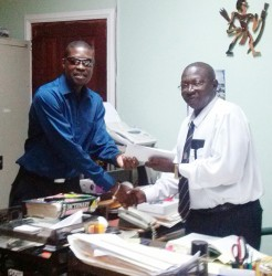 AFC General Secretary David Patterson (left) handing the motion over to Clerk of the National Assembly Sherlock Isaacs.