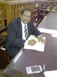 AFC Vice-Chairman and MP Moses Nagamootoo signing the motion yesterday. (AFC photo)