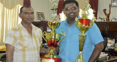 Minister of Tourism Irfaan Ali, right and Trophy Stall CEO Ramesh Sunich show off some of the trophies which will up for grabs at today's sporting events of the Guyana Festival.