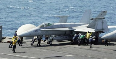 Sailors guide an F/A-18C Hornet assigned to the Valions of Strike Fighter Squadron (VFA) 15 on the flight deck of the aircraft carrier USS George H.W. Bush (CVN 77) in the Gulf, in this handout image taken and released on August 8, 2014.