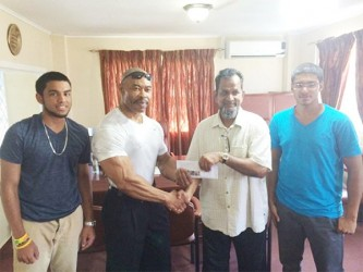 CEO of Mohamed's Enterprise, Nazar Mohamed presenting the cheque to Hugh Ross yesterday. Mohamed is flanked by his nephews Robin Sookraj (left) and Christopher Morgan.