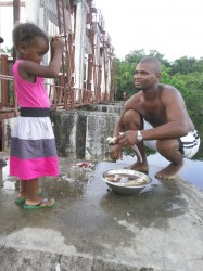 Richardo Harris (my brother-in-law) cleans some fish he caught while his daughter Genisa looks on at the GuySuCo five gate compound at Bartica
