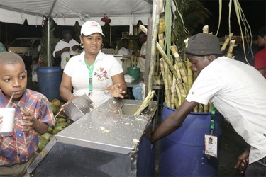 Refreshingly sweet: Quenching the thirst for cane juice on the opening day of the Guyana Festival on Friday at the National Stadium.