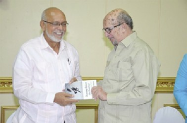 President Donald Ramotar (left) receives a copy of the book ' Dancing between the Raindrops' from its author Dr Rudy Insanally.(GINA photo)