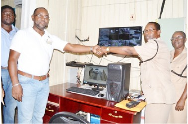 General Manager of the Demerara Harbour Bridge, Rawlston Adams (left) and Commander of  'A' Division, Clifton Hicken during the commissioning of the surveillance system at the Police Operations Room, Brickdam Police Station. (GINA photo)