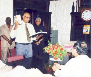 Vishnu Persaud, Deputy Chief Election Officer/Deputy Commissioner of Registration taking the Oath of Office which was administered by Chief Justice Ian Chang (seated).  Looking on are Dr. Steve Surujbally (third from left), Chairman of GECOM and Keith Lowenfield, Chief Election Officer. (GECOM photo)