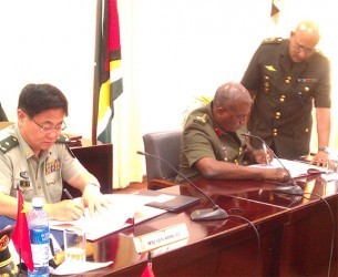 (From right) Major General Kong Li signs a US$4.8M Military Aid-Package with Chief of Staff Brigadier-General Mark Phillips yesterday at the opening ceremony of the Guyana-China Bilateral Staff Conference 2014 to strengthen the military in Guyana.