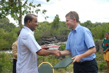President Bharrat Jagdeo (left) and Norwegian Minister of International Development and the Environment, Erik Solheim, shake hands after the completion of the signing of the Memorandum of Understanding between Guyana and Norway in November 2009 here. (GINA photo)