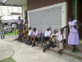 A group of pensioners waiting outside of the Bourda Post Office at lunch