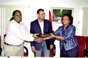 Permanent Secretary of the Ministry of Natural Resources and the Environment Joslyn Mackenzie and Guyana's UN Resident Coordinator and UNDP Resident Representative Khadija Musa exchange copies of the signed agreement on biodiversity practices, while Minister of Natural Resources and the Environment Robert Persaud looks on. (Government Information Agency photo)