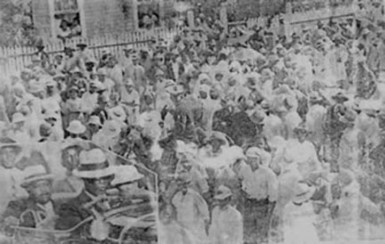 A crowd greets Marcus Garvey on his arrival at the home of Dr Wills at Lot 190 Charlotte Street, Georgetown in October 1937.
