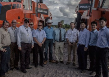 Prime Minister Samuel Hinds and Minister of Natural Resources Robert Persaud stand with representatives from Troy Resources Guyana Inc., Farm Supplies Ltd. and Doosan in front of some of the equipment. (Photo by Michael Fernandes)