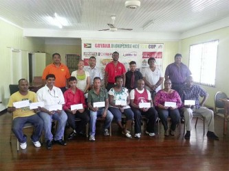 Representatives from various charitable organizations displaying their cheques in the presence of members of the organizing committee of the Guyana Independence T20 Cup, 2014.