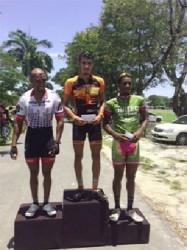 Alanis' Paul DeNobrega atop the podium, flanked by Robin Persaud, and Mario King.
