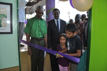 PNCR Leader David Granger (left) watches on approvingly as the ribbon declaring the institute open is cut. (PNCR photo)