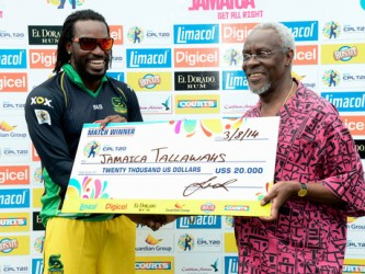 Former Prime Minister of Jamaica P.J. Patterson (right) presents Christopher Gayle, captain of the Jamaica Tallawahs, with the winners' cheque shortly after they defeated the Barbados Tridents in the Caribbean Premier League Twenty20 cricket match at Sabina Park on Sunday