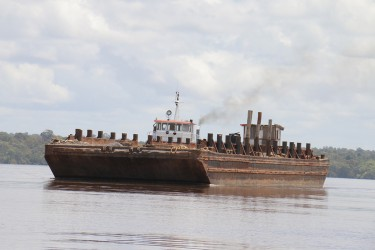 Vaitarna's barge heading up to Wineperu on Tuesday for logs. The India-based company continues to export logs but is yet to set up its promised processing plant. (Arian Browne photo)