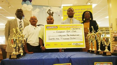 Courts Marketing Manager, Pernell Cummings (2nd right) and Public Relations Officer, Roberta Ferguson (right) with the sponsorship cheque in the presence of David Mohamed (3rd left), Chatterpaul Deo (2nd left) and Guy Griffith.