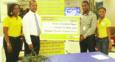 Courts' Marketing Manager, Pernell Cummings hands over the sponsorship to president of the AAG, Aubrey Hutson following the launch of the 10km event yesterday at the furniture giant's Main Street store.