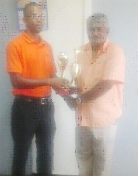 Chief Executive Officer (CEO) of the Berbice Bridge Company Incorporated (BBCI) Omadatt Samaroo hands over the trophies to Johnny Marcus of the Guyana Draughts Association.