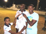 Newest Floodlights Softball Cricket Club member Shivnarine Chanderpaul receives his team shirt from the youngest Floodlights player eight year old Romeo Deonarine.