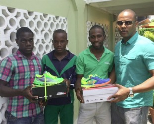 Cleveland Thomas (2nd right) and Matthew McKenzie (2nd left) received athletic gear and supplements yesterday from Kwame Ridley (left) and Carey Griffith.