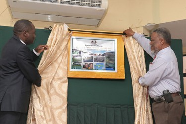 Vice Chancellor of the University of Guyana Jacob Opadeyi (left) and Prime Minister Sam Hinds unveil a plaque featuring the new collection of commemorative stamps launched yesterday in observance of UG's 50th anniversary. (See story on page 17) (Arian Browne photo)