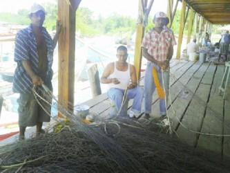 Parmeshwar Jainarine and workers mending fish seines at the fisheries