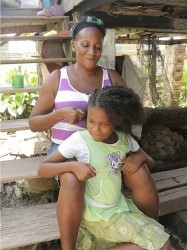 Verna Sam sits on her step combing her daughter's hair. Photo by Arian Browne