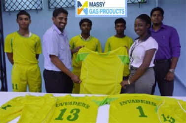 Invaders Captain Vaickesh Dhaniram receives the uniforms from Massy Gas Products Customer Services Officer Elicia Chapman while some members of the team look on.