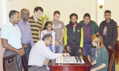 Some of the competitors in the Umada Cup observe Sport Minister Dr Frank Anthony as he makes the first move against National Junior Champion Su Haifeng Su to signal the start of the tournament.